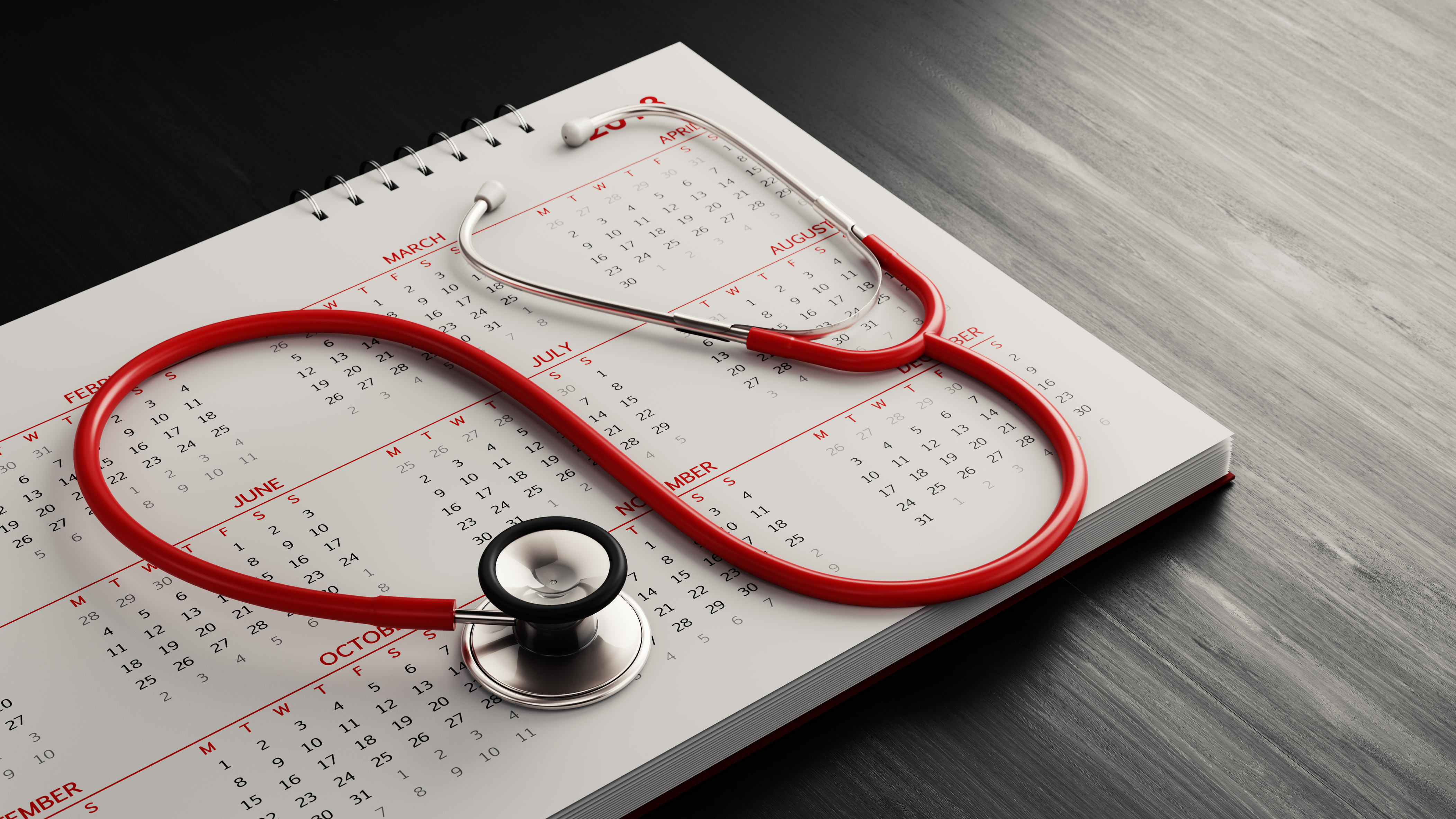 Red Stethoscope And A Calendar On Black Wood Surface
