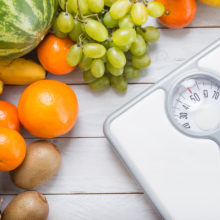 Stack of fruits and white weight scale on wooden board.